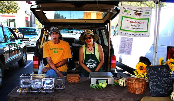 Spivia (right) and Yvonne (left) Manning sit in the shade and sell their produce at the Elk Grove Farmers Market on Aug. 31.