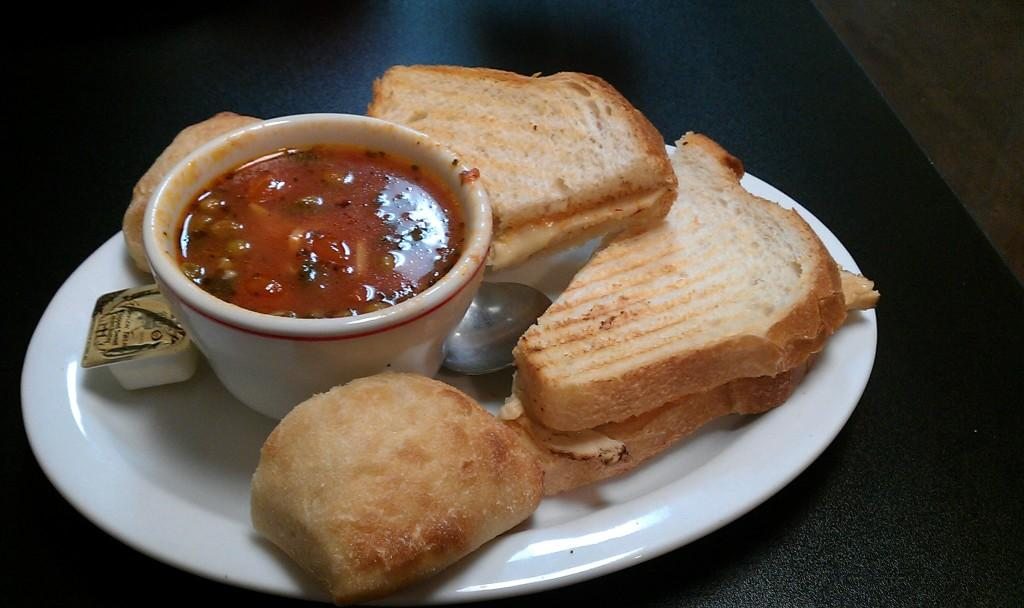 A grilled turkey panini accompanied by a bowl of vegetable minestrone soup from Bravo's Soup and Sandwich Shoppe.