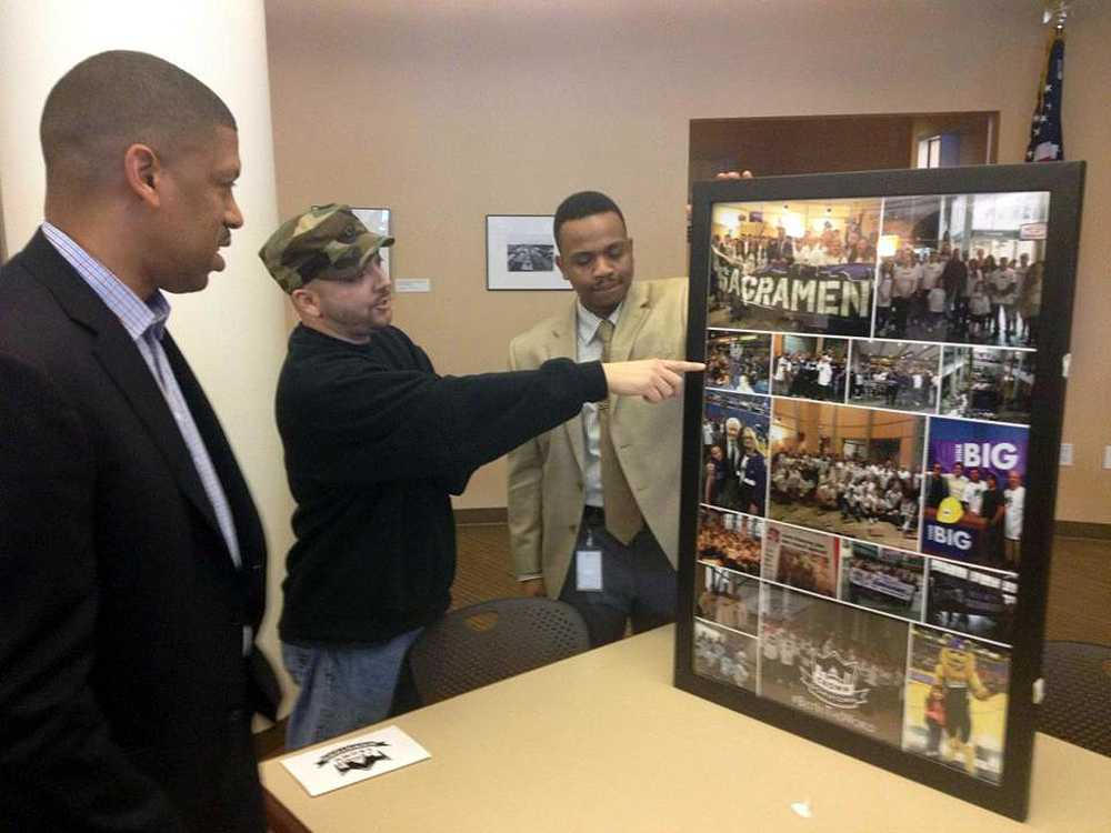 CRC adjunct counselor Mike Tavares presents Sacramento Mayor Kevin Johnson with a gift, a collage of photos, in Sacramento City Hall on Jan. 30.