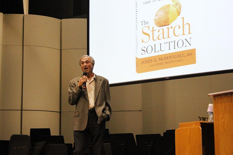 Dr.+John+McDougall+speaks+during+a+One+Book+lecture+about+healthy+eating+habits+in+the+Recital+Hall+on+Oct.+23.+Copies+of+McDougall%27s+book+%22The+Starch+Solution%22+was+sold+at+the+event.+