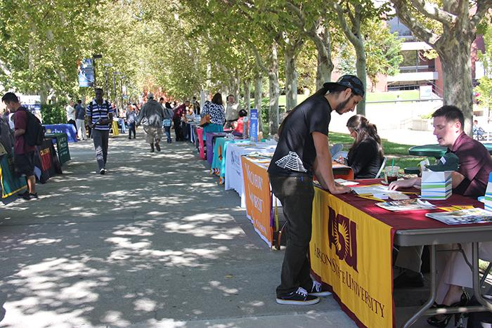 Students+who+attend+Cosumnes+River+College+visit+the+tables+set+up+by+various+four-year+colleges+in+preparation+for+transfer+at+the+fall+Transfer+Day+Fair+in+September+2013.+Attending+a+two-year+college+similar+to+CRC+gives+students+a+leg+up+educationally+and+financially+when+they+transfer+to+the+next+level+of+education.
