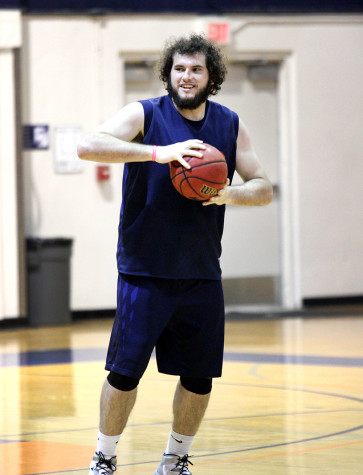 Sophomore forward Jaycob Velasco smiles as he grips a basketball at team practice on March 3. The Hawks are preparing for a quarterfinal matchup with Fresno City.