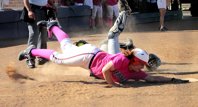 Sophomore outfielder Jessica Venturelli, in her pink uniform for the days breast cancer awareness drive, dives for home base in an attempt to tie the score against the American River College Beavers sophomore catcher Jordyn Bradley on April 19. Venturelli was called out, and the Hawks lost the second game of their double header against ARC, 5-4.