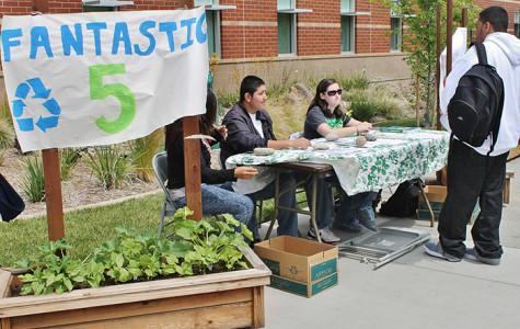 Fantastic Five members Kathryn Villagrana, Ramiro Madrigal and Bethany Mulligan work a table during the campus Earth Day event outside the Winn Center, to explain their project and collect food to donate to Food Not Bombs on April 24.
