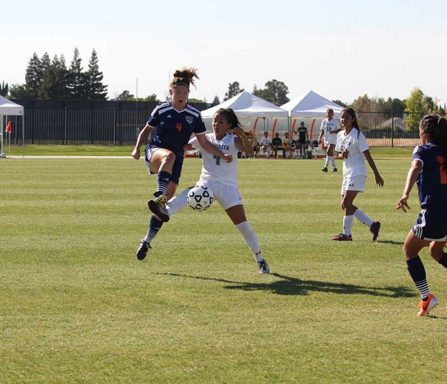 CRC Hawks freshman midfielder Kate Burkhardt leaps into the air for the ball, connecting with an opposing player from Evergreen Valley College Hawks.  Burkhardt and her team defeated the EVC Hawks 4-3 but the close game underscores the rough season start for the team.