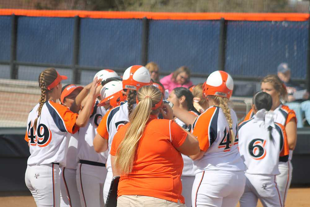 Hawks players celebrate at home plate and pat the helmet of sophomore utility Hanna Miller after Miller's first inning home run brought them an early lead in game one against Butte College.