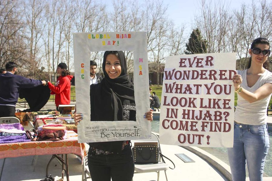 Jamie Meastas, 22, an undeclared major (left) and 20-year-old cinematography major Yalda Biglari (right) took part in the Muslim Student Association event which included interactive props like the picture frame held by Jamie that allowed students to take a picture of themselves trying on a hijab on Feb. 25.