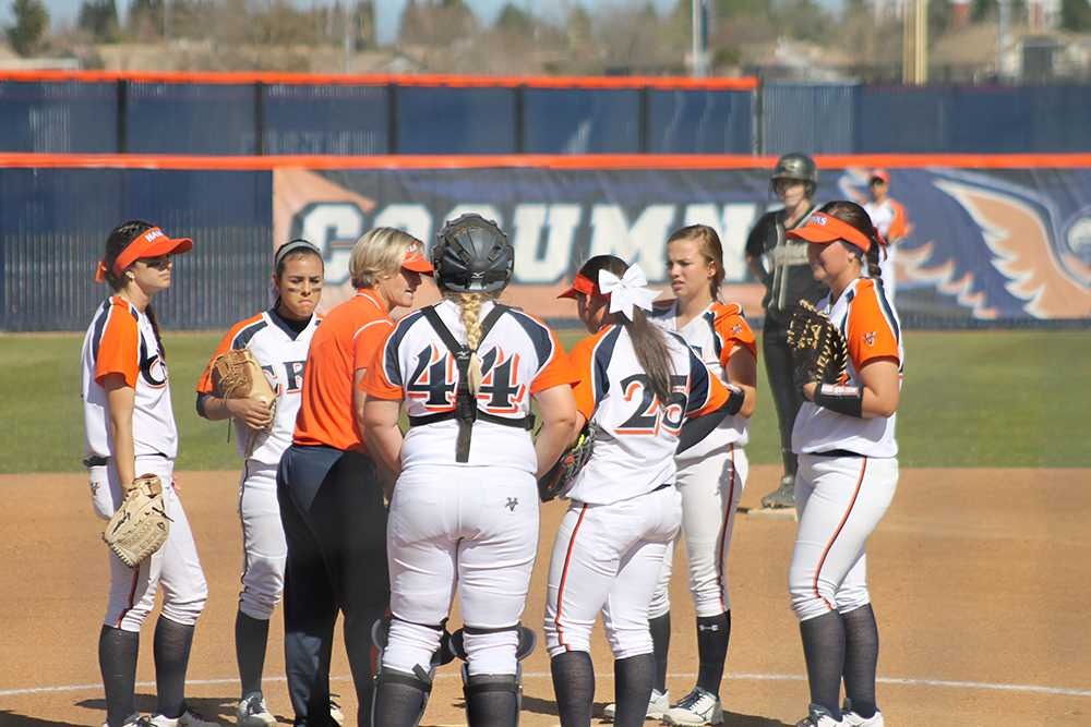 The softball team meeting with Coach Kristy Schroeder on the mound to talk during one of their double header games against Butte College on Feb. 27.