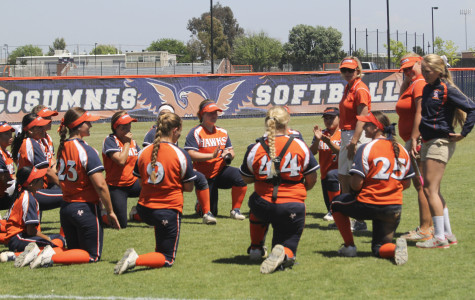 The Hawks softball team talking with head coach Kristy Schroeder after their 6-1 win against Fresno City.