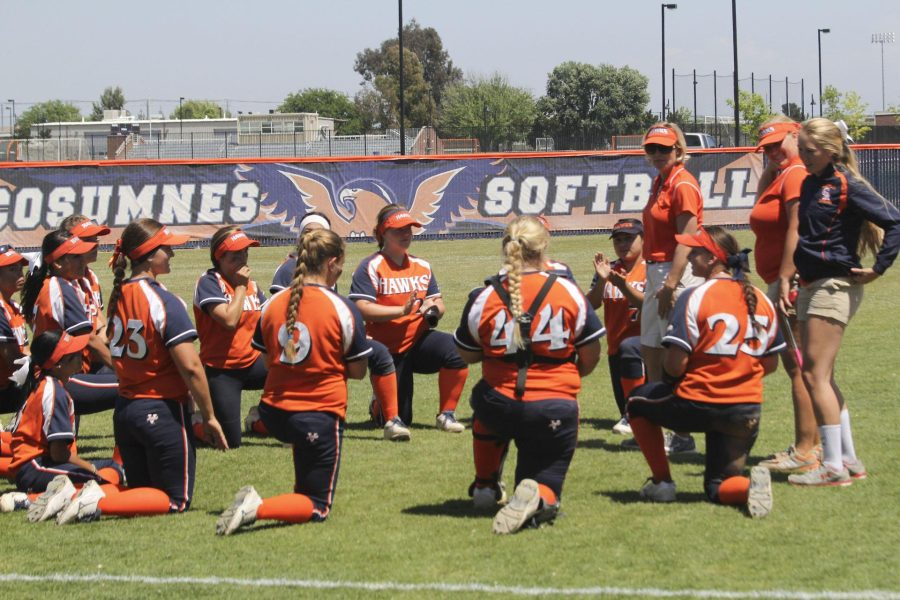 The+Hawks+softball+team+talking+with+head+coach+Kristy+Schroeder+after+their+6-1+win+against+Fresno+City.