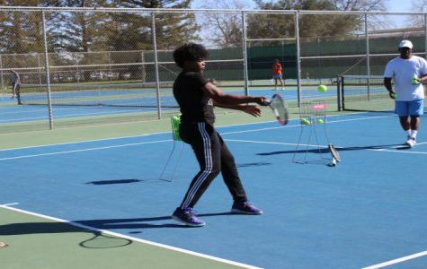 Freshman player Paradise Whalen works on her forehand with Assistant Coach Edmund Carter during practice.