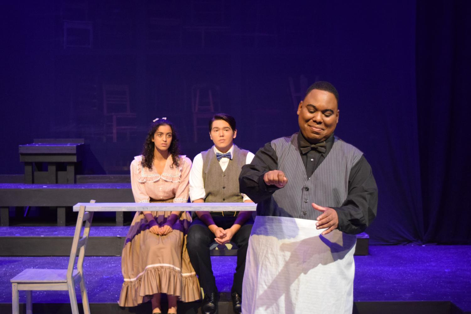 'Store Manager' (Coleman Daniel) scoops ice cream for young lovers, Emily (Sara Alnassiri) and George (David Johnson) in a performance of 'Our Town' on Oct. 13.