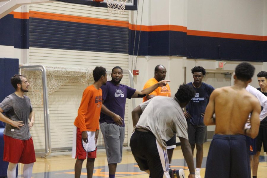 Men's basketball head coach Jonathan James runs the new team through drills.