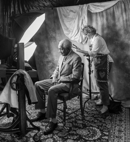 In a photo taken by her husband, who served as an assistant during the project, Professor Kathryn Mayo preps one of her subjects, F.D. Reese, before taking his photo as part of her sabbatical portrait project