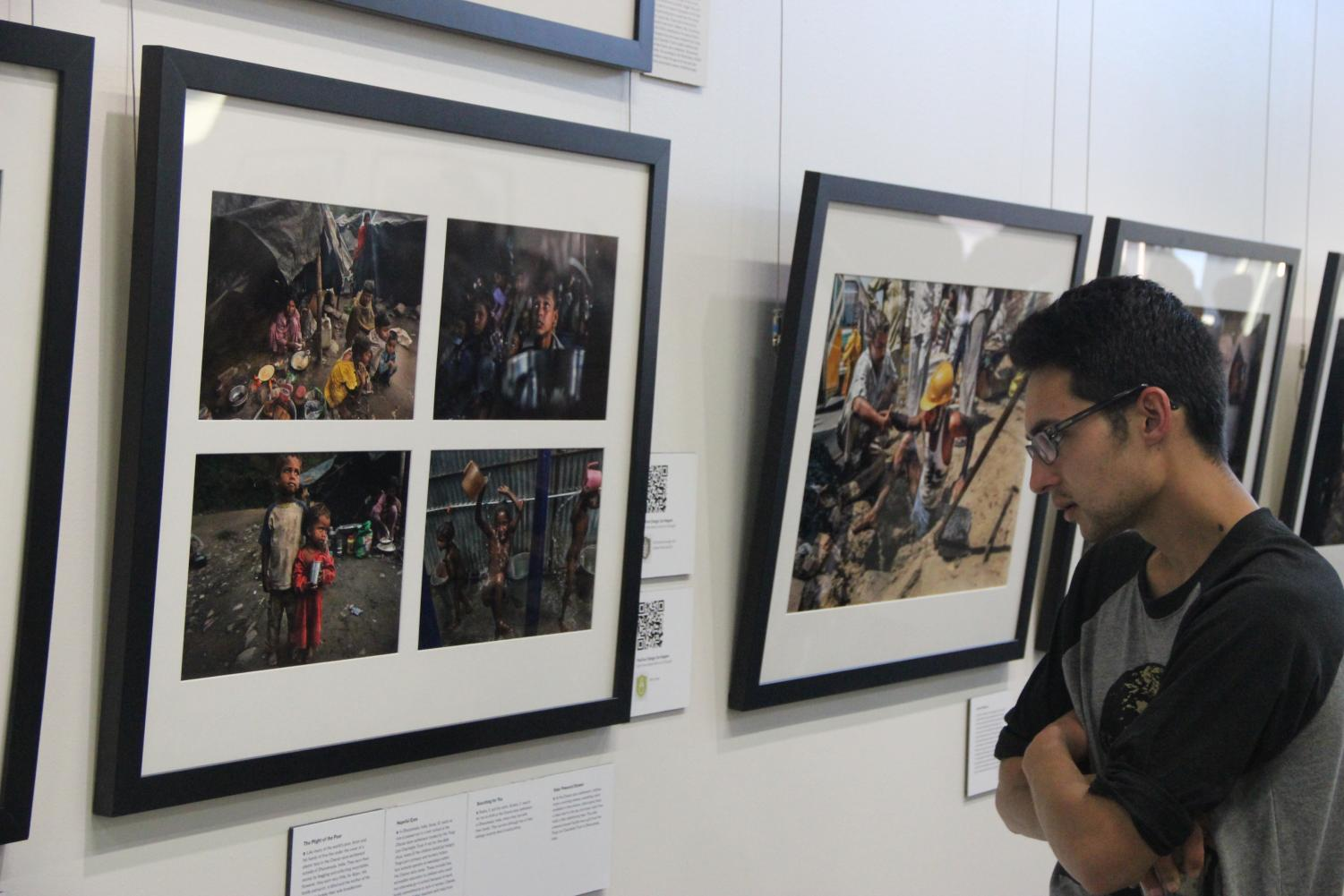 Austin Gonzales browses the photo collection by Renne C. Byer, showcasing poverty around the world.