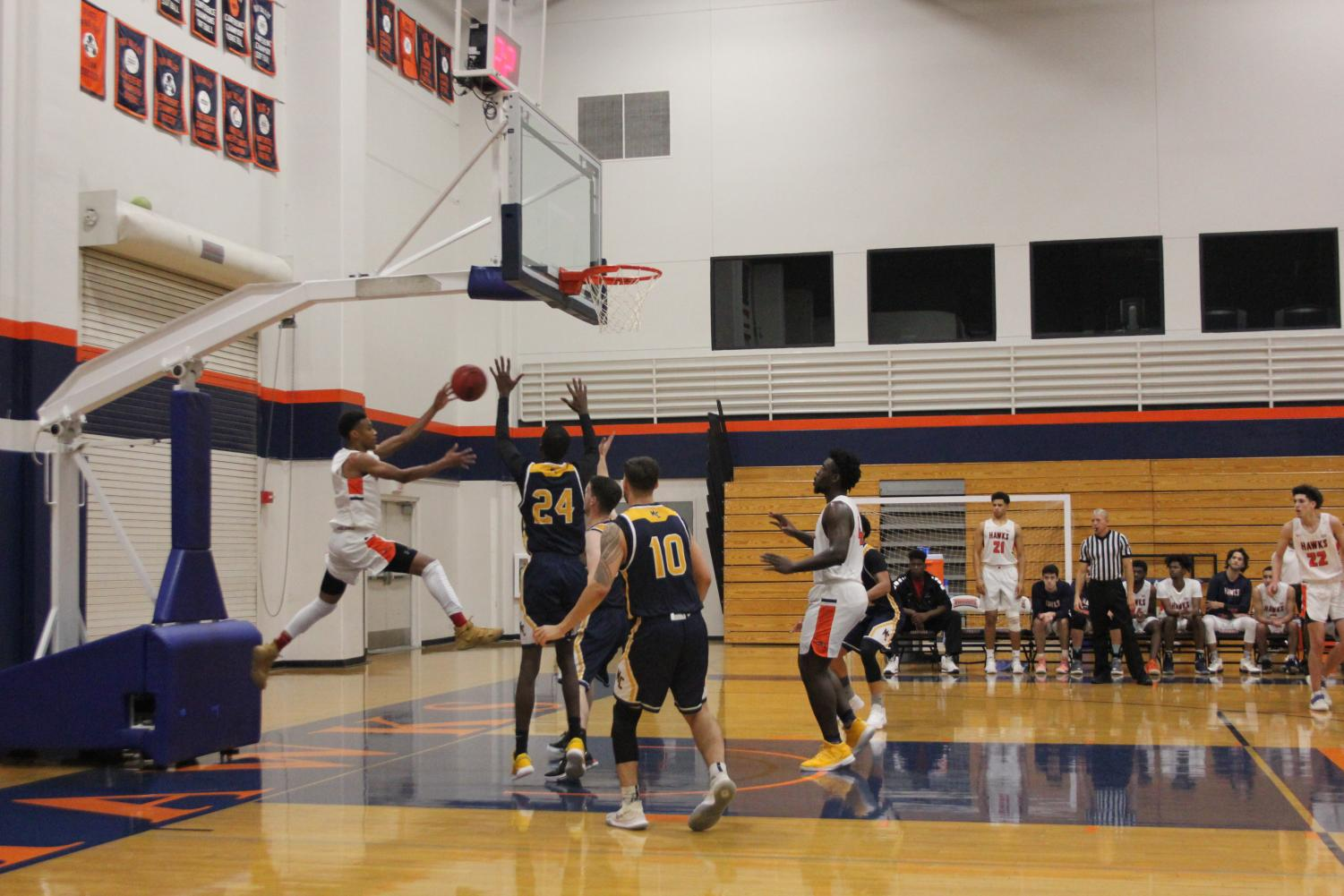 Sophomore Kenneth Cooley leaps to save the ball from going out of bounds during the Hawks 80-62 win against Merced on Nov. 30.