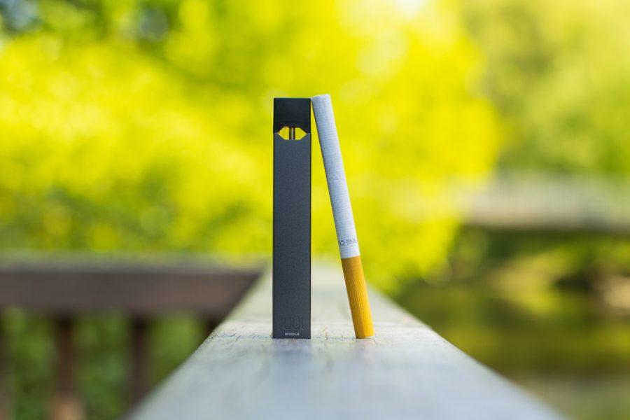 A juul cigarette stands next to a regular cigarette.