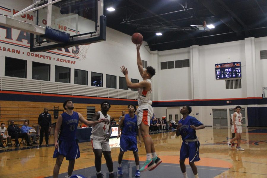 Sophomore forward Drew Buggs goes for a turnaround hook shot after a pump fake on Tuesday against Modesto. Bugg's 17 points helped the Hawks get a much needed win as they fight for a playoff spot.