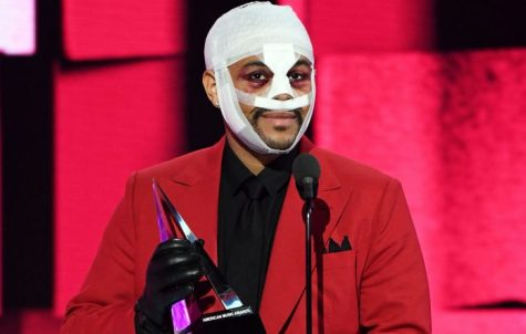 The Weeknd accepting an award at the American Music Awards. His face is bandaged and beaten as he